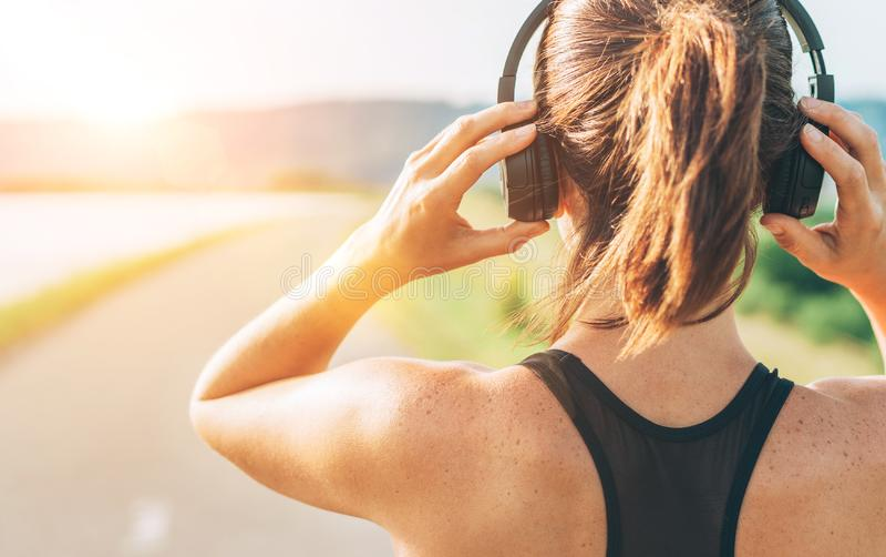 Nära övre bild av tonåringen som justerar trådlös hörlurar, innan att starta att jogga och att lyssna till musik arkivbilder