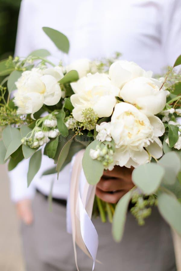 Nära övre bouqet av blommor som håller vid brudgummen arkivfoton