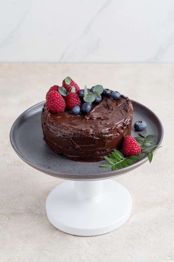 Nära övre chokladkaka med bärdekoren på den gråa plattan på ljus bakgrund arkivfoton