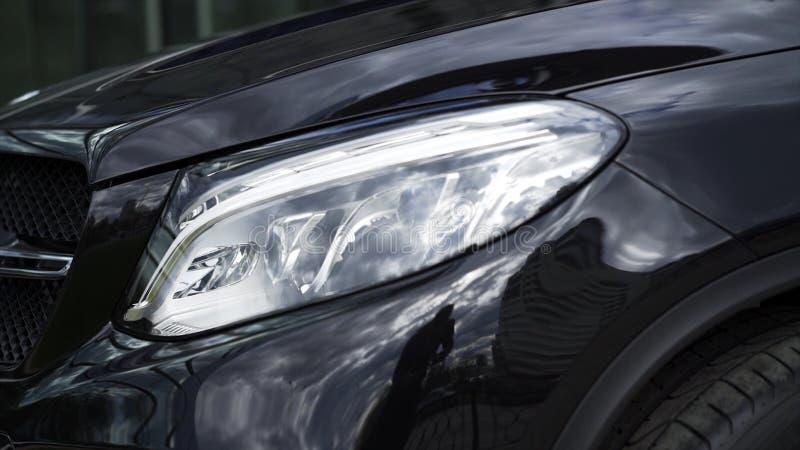 Nära övre detalj för en av de LEDDE billyktorna av en modern svart bil materiel Yttre detalj, billykta av ett prestigefullt arkivfoto