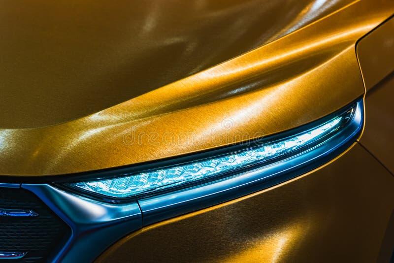 Nära övre detaljskott av billyktan av den moderna lyxiga sportbilen Främre sikt av supercaren Begrepp för bakgrund för motor royaltyfri fotografi