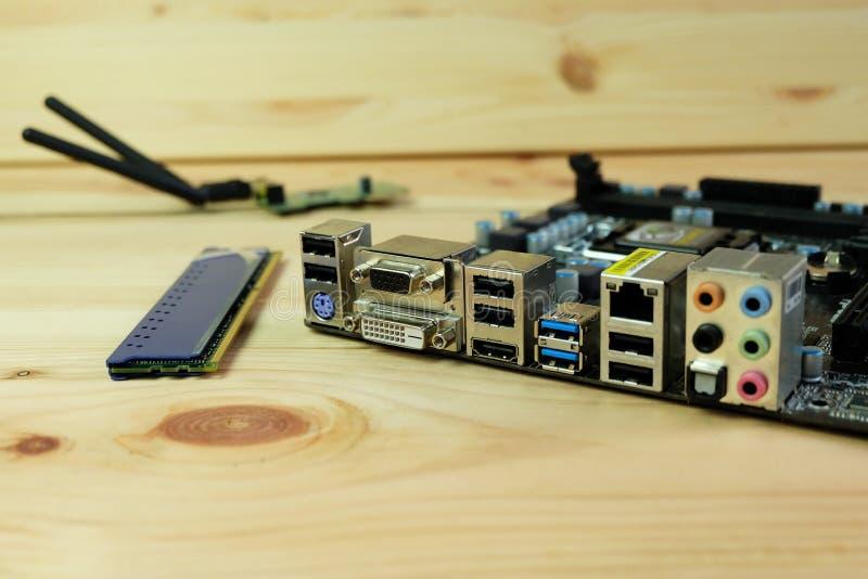 Nära övre dvi, vga, USB 3 0, HDMI och olika anslutningsportar av datormoderkort på trä royaltyfria bilder
