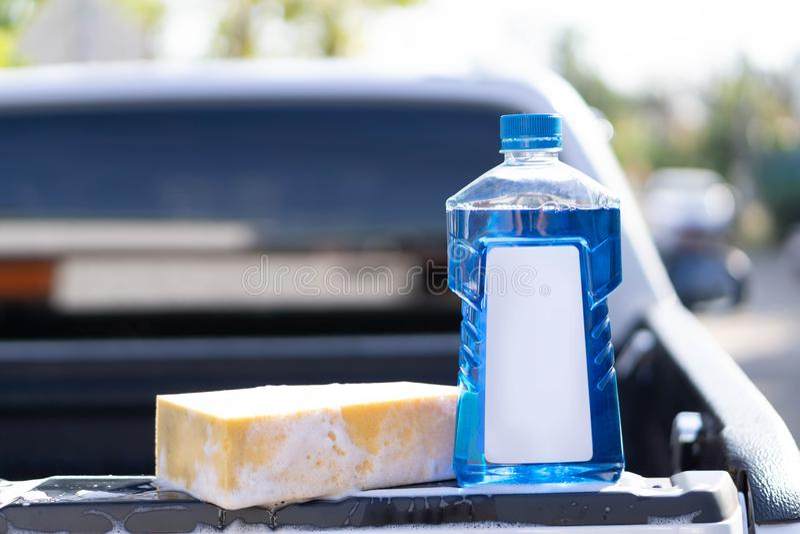 Nära övre flaska av biltvätttvål med den gula svampen för tvätt, selektiv fokus arkivbild