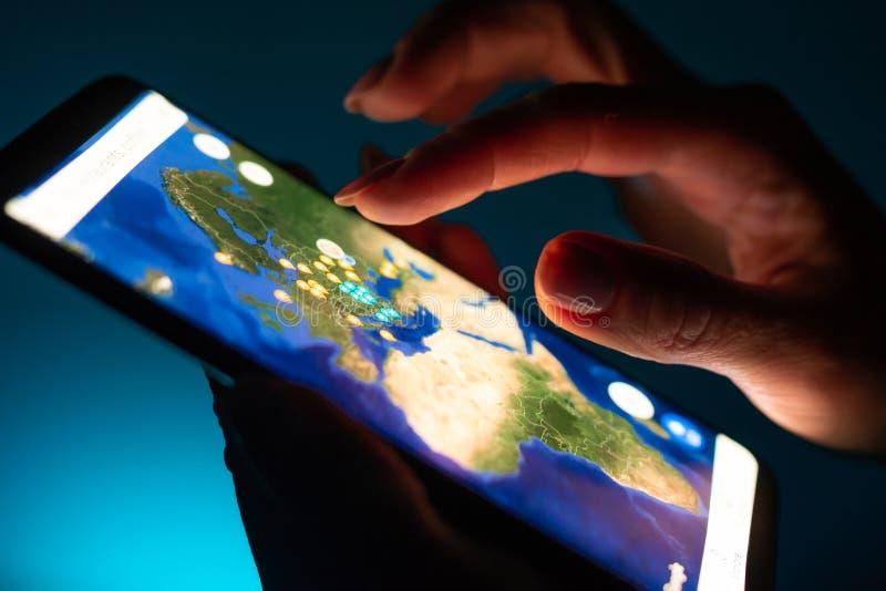 Nära övre flickahand genom att använda smartphonen med den Google Maps appen royaltyfri foto