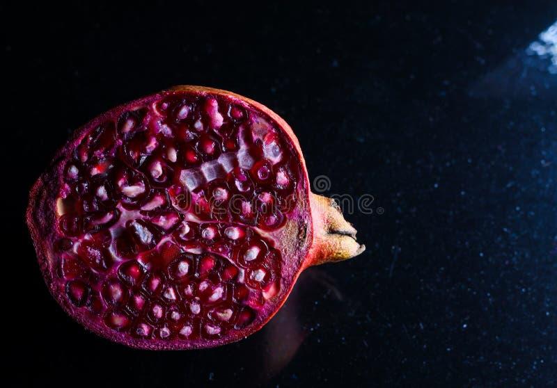 Nära övre foto av den klippta granatäpplet i mörk bakgrund royaltyfria foton