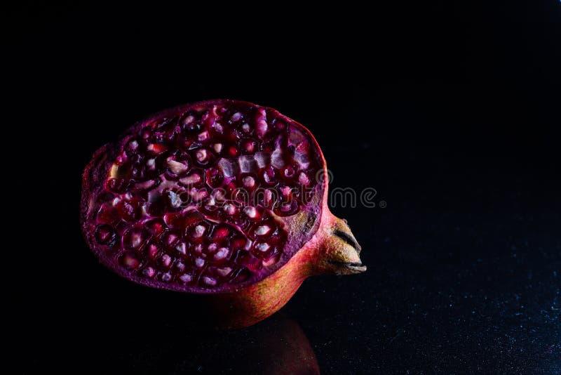 Nära övre foto av den klippta granatäpplet i mörk bakgrund arkivbild