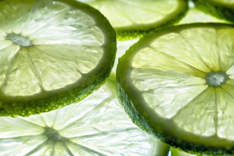 Nära övre foto av naturliga glödlimefruktskivor i ljus- och skenbakgrund arkivbild
