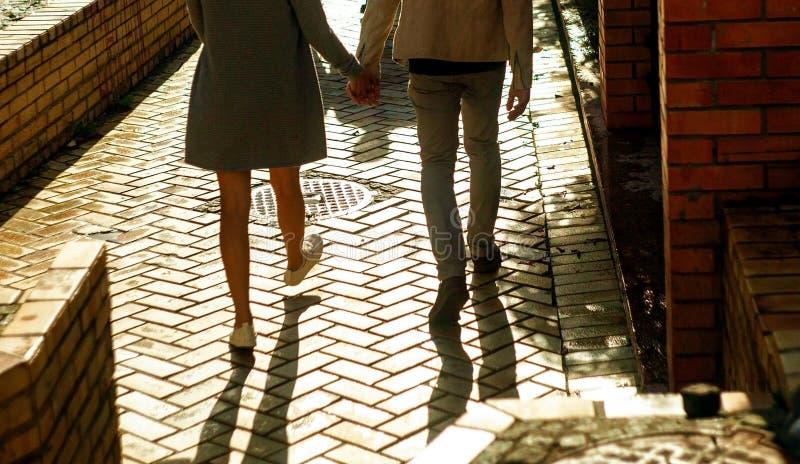 Nära övre foto av pars ben som går på gatan på solnedgången royaltyfria bilder