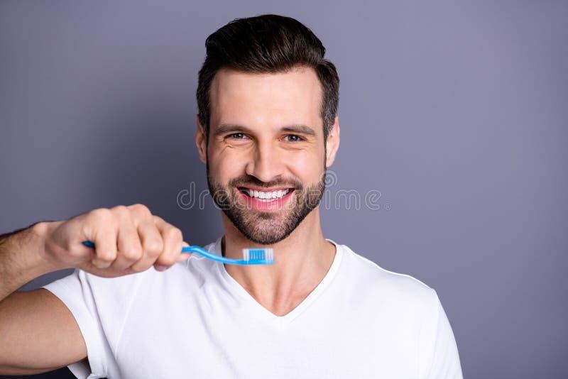 Nära övre foto som förbluffar honom honom hans macho rengörande tandborste för personlig utrustning för nytt krimskrams för hand  royaltyfria bilder