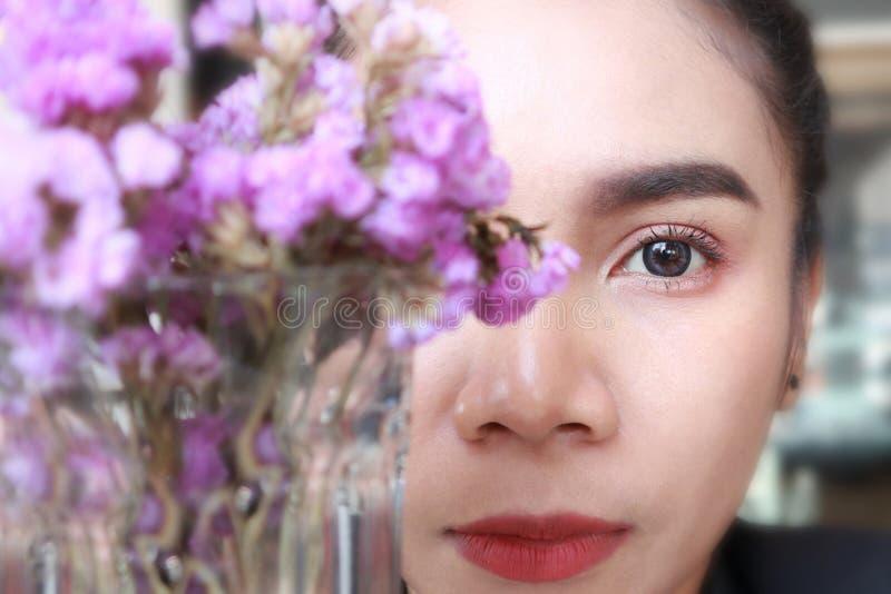 Nära övre framsida av den asia kvinnan med blomman, den härliga ögonkvinnan och framsidan royaltyfria bilder