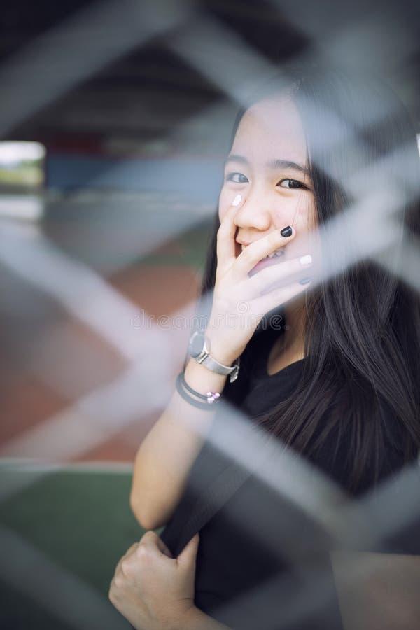 Nära övre framsida av den härliga asiatiska tonåringen som kopplar av i skolastadion royaltyfria foton