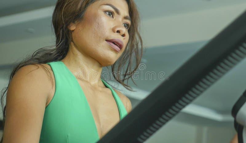 Nära övre framsida av den unga beslutsamma och fokuserade asiatiska kvinnan på idrottshallen som gör genomkörare i den ellipsform royaltyfria foton
