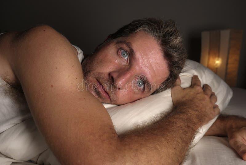 N?ra ?vre framsidast?ende av den s?mnl?sa och vakna attraktiva mannen med ?gon vitt som ?r ?ppna p? natten som ligger p? s?ng som royaltyfri foto