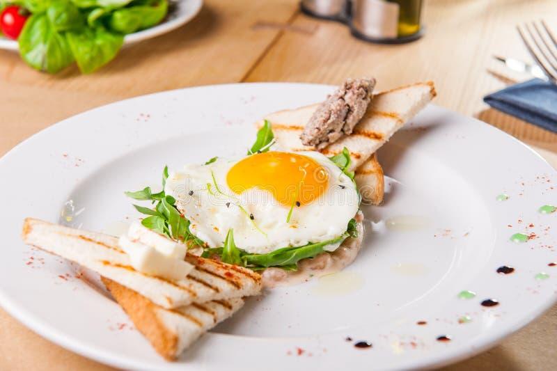 Nära övre frukost med stekte ägg, rostade bröd och köttpate på den vita plattan på den tjänade som trätabellen Selektiv fokus, ko arkivfoton