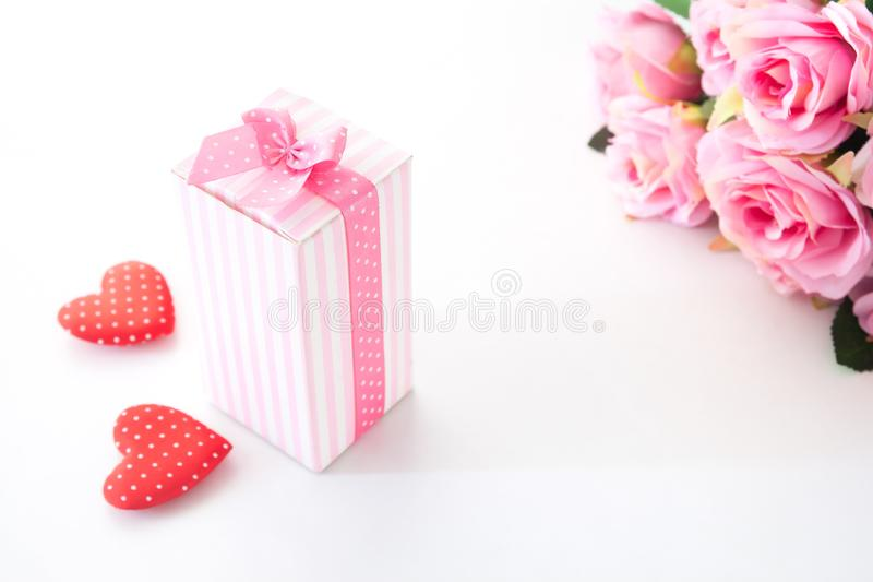 Nära övre gåvaask på vit bakgrund med rosa rosor och hjärta på vit royaltyfria bilder