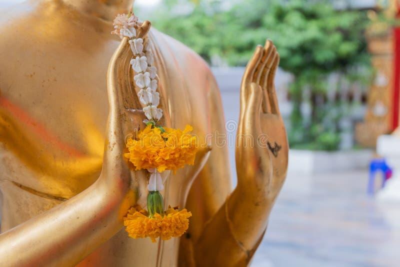 Nära övre hand av girlanden för blomma för håll för färg för Buddhastaty den guld- i tempel arkivfoto