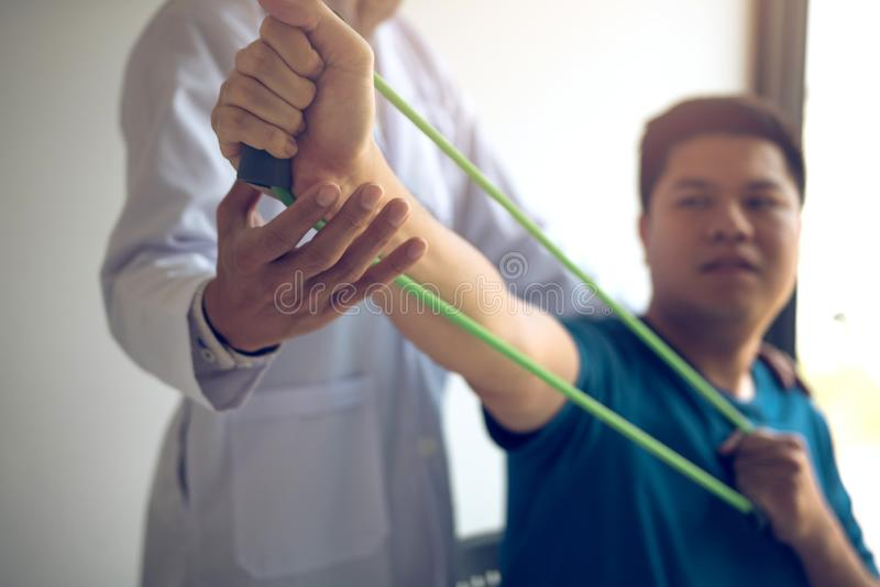 Nära övre handpatient som gör sträcka övning med en böjlig övningsmusikband och en hand för fysisk terapeut för att hjälpa i klin arkivfoto