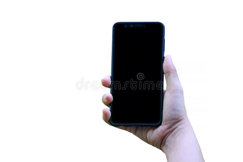 N?ra ?vre kvinnahand som rymmer modern svart smartphone?tl?je upp i vertikal position med den isolerade tomma sk?rmen p? vit bakg arkivfoto