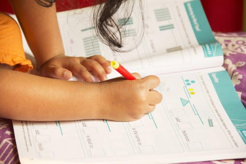 Nära övre liten flicka som gör hennes studier, Pune, Maharashtra, Indien arkivbild