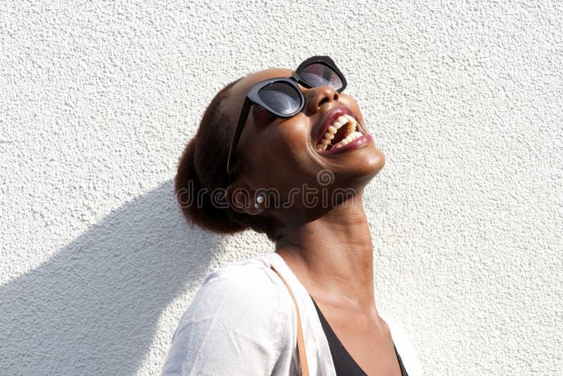 Nära övre modestående av den lyckliga svarta kvinnan med solglasögon royaltyfria foton