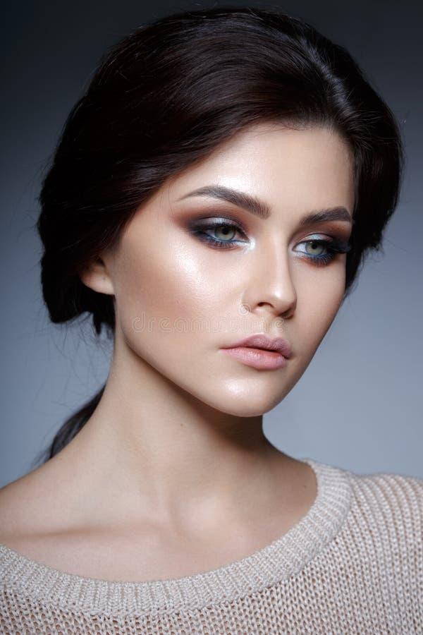 N?ra ?vre profilst?ende av en behagfull ung kvinna med perfekt makeup och ny hud, p? en gr? bakgrund arkivbilder