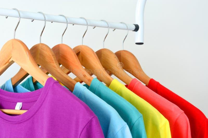 Nära övre samling av färgrika regnbåget-skjortor som hänger på träklädhängare arkivfoton