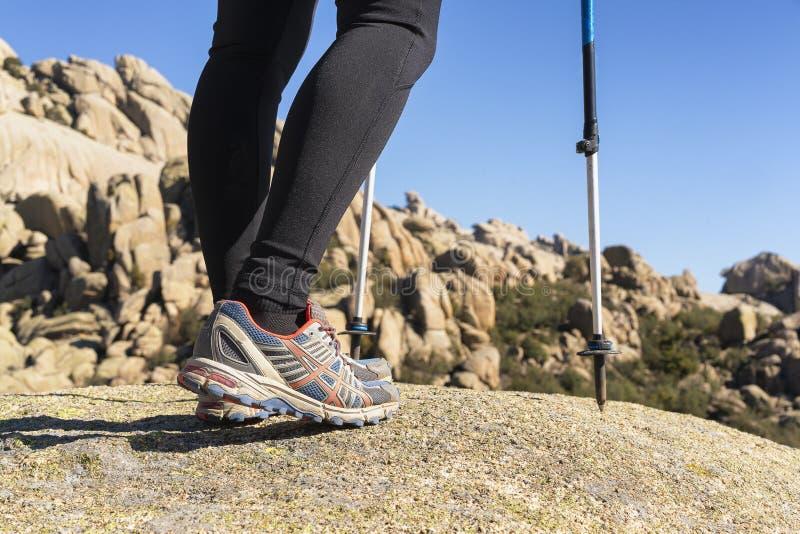 Nära övre sikt av benen av en kvinnafotvandrare i La Pedriza, nationalpark av bergskedja av Guadarrama i Manzanares el Real, royaltyfri bild