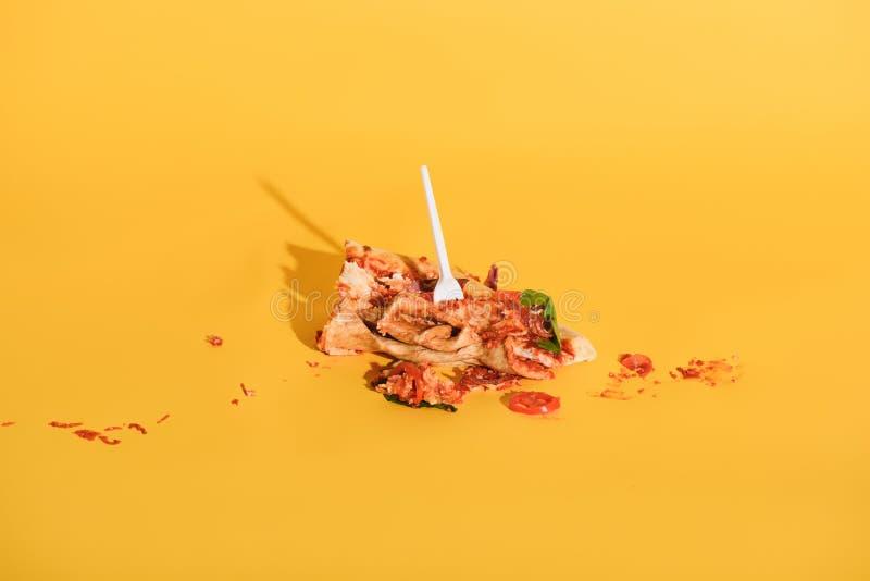 nära övre sikt av den disponibla gaffeln i slagit stycke av pizza arkivfoto