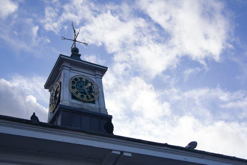 Nära övre sikt av det gamla klocka-, kompass- och vindtecknet på hustaket arkivbilder