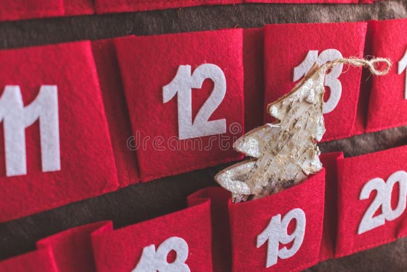 Nära övre sikt av en röd och brun textilAdventkalender med data och en julgrangarnering i ett fack fotografering för bildbyråer