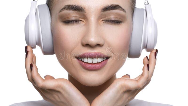 Nära övre sikt av en ung kvinna som lyssnar till musiken via hörlurar Isolerat p? vit royaltyfri foto