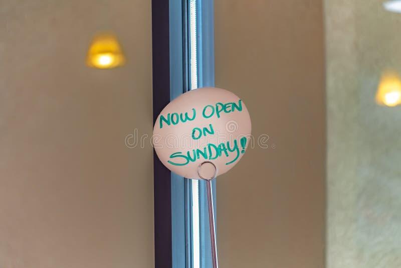 Nära övre sikt av ett handskrivet tecken som läser nu öppet på söndag arkivfoton