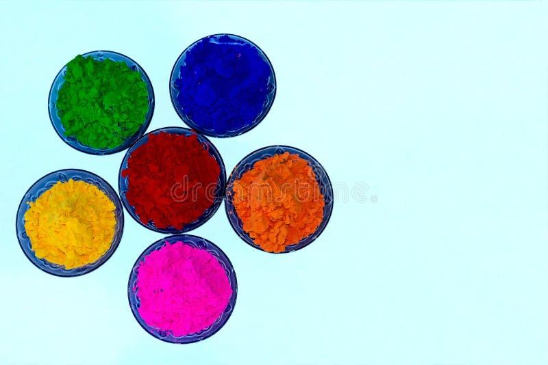 Nära övre sikt av färgrika organiska Holi pulver i blåa färgexponeringsglasbunkar royaltyfri foto