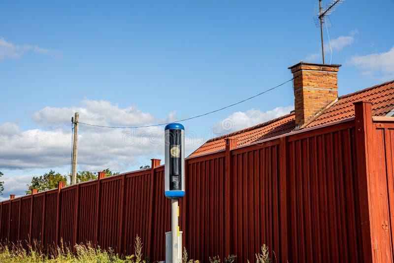 Nära övre sikt av hastighetskameran på det röda staketet och blå himmel med vit molnbakgrund arkivfoto