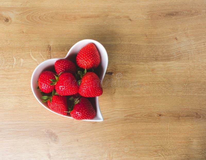 N?ra ?vre sikt av jordgubbar och en r?d blomma i en vit hj?rta formad bunke p? tr?bakgrund royaltyfri foto