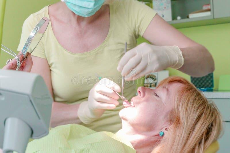 Nära övre sikt av kvinnatandläkaren som arbetar på hennes patienttänder i tandläkarekontor royaltyfria bilder