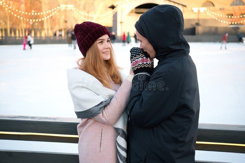 Nära övre sikt av par som rymmer händer i vinter nära isisbana arkivbild