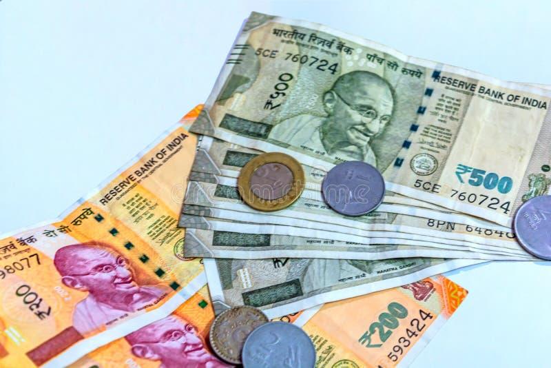 Nära övre sikt av splitterny indier 200, 500 rupier sedlar och några mynt på vit bakgrund royaltyfri foto