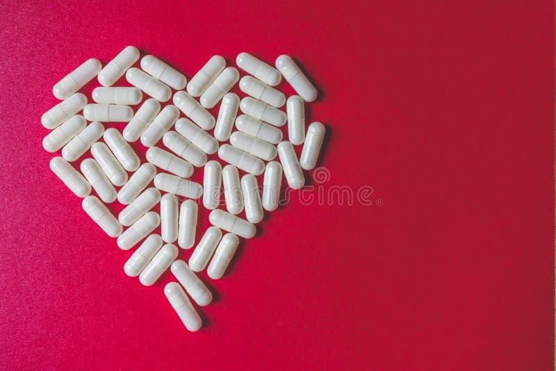 Nära övre sikt av vita kapslar som bildar en hjärta på röd bakgrund med utrymme royaltyfri fotografi