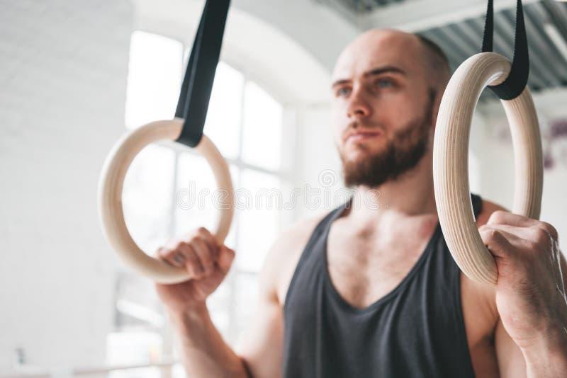 Nära övre sikt på den manliga gymnasten som gör genomkörare på gymnastikcirklar i arg idrottshall royaltyfria bilder