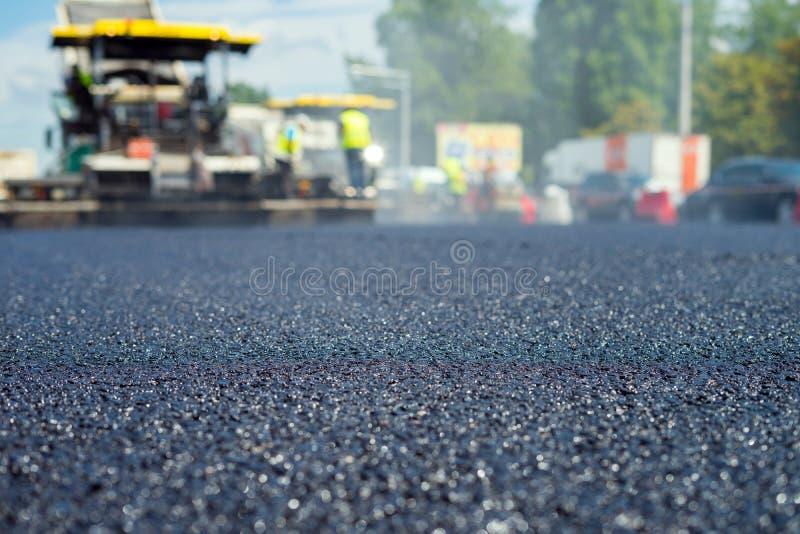 Nära övre sikt på den nya asfaltvägen på vilken speciala utrustning fungerar Suddigt foto av konstruktionsplatsen fotografering för bildbyråer