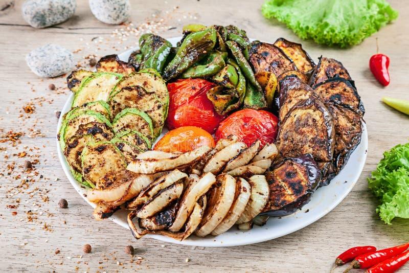 Nära övre sikt på grillade grönsaker på den vita plattan som tjänas som på den vita trätabellen tomat, peppar, aubergine, zucchin royaltyfri fotografi