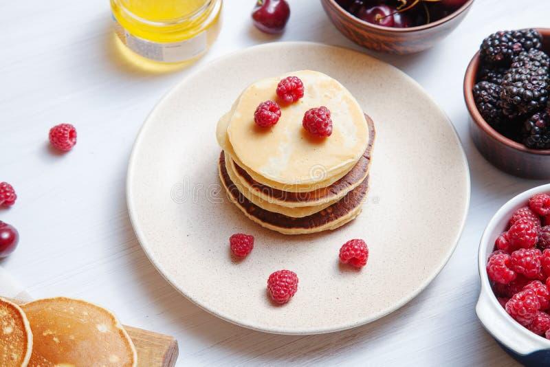 Nära övre sikt på hemlagade klassiska amerikanska pannkakor med det ny bäret och honung, morgonljus på vit bakgrund Mat f?r arkivfoto