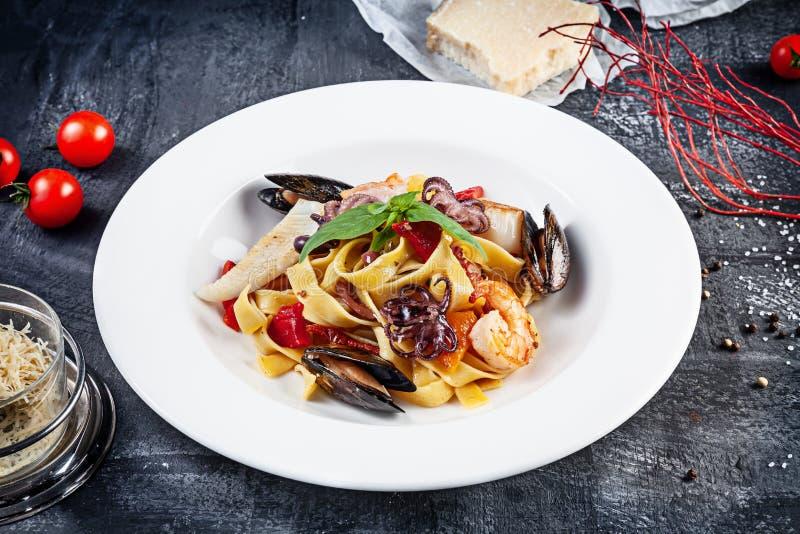 N?ra ?vre sikt p? traditionell italiensk pasta med skaldjur som tj?nas som p? m?rk bakgrund Plan lekmanna- italiensk kokkonst med royaltyfri foto