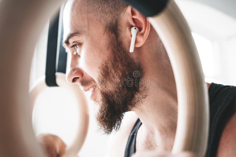 Nära övre sikt till och med gymnastikcirklar på den skäggiga manliga idrottsman nen som bär trådlös hörlurar i sportkorridor royaltyfria bilder