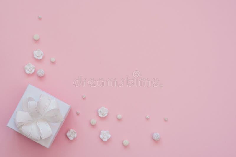 N?ra ?vre skott av den lilla vita g?van som sl?s in med det vita bandet p? rosa bakgrund Minsta begrepp Lekmanna- l?genhet Top be arkivbild