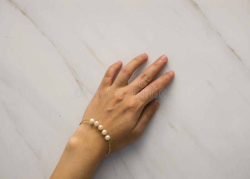 Nära övre skott av det härliga guld- armbandet med pärlor på woman&en x27; s-hand royaltyfria foton