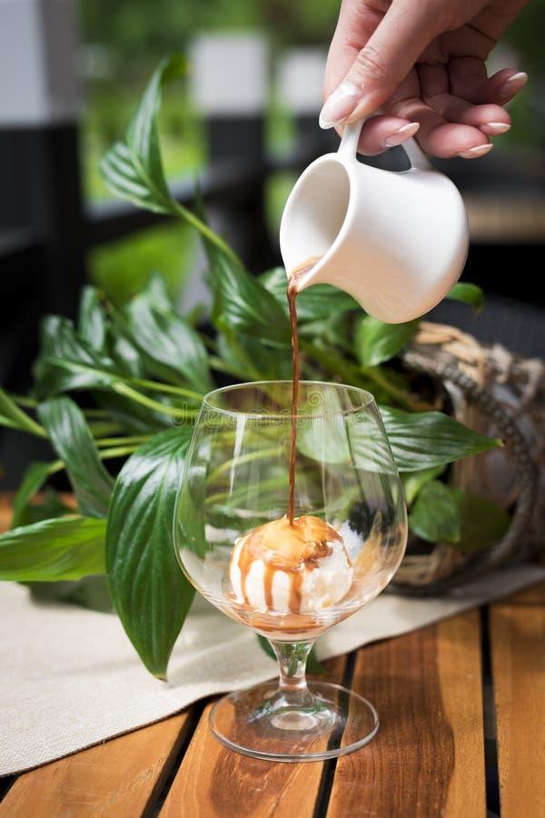 Nära övre skott av ett hällande espressokaffe för hand på Vanilla Ice kräm i ett exponeringsglas, efterrätt, på den lantliga trät royaltyfri fotografi