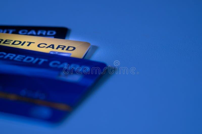 Nära övre skott av plast- kreditkortar med gul guld för selektiv fokus och blå signalbakgrund royaltyfria foton