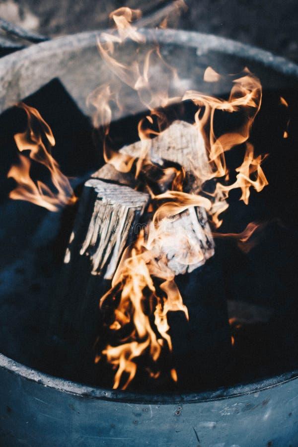 Nära övre skott av stycken av träbränning med brand i en stor kruka fotografering för bildbyråer
